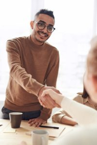 Man smiling and holding out a hand shake